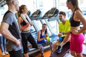 Люди улыбаются после тренировки в фитнес-клубе