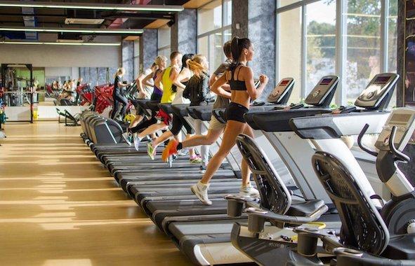 Девушка бежит по беговой дорожке в фитнес-клубе